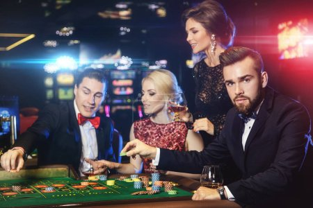 Young rich people playing roulette in casino