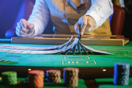 Professional croupier during cards shuffle in the casino