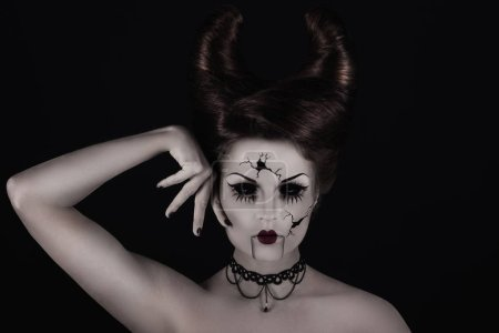 Model in creative image for Halloween. Spooky porcelain doll with horns on her head.
