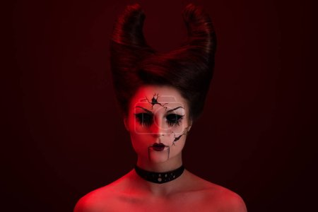 Model in creative image. Spooky porcelain doll with horns on her head.