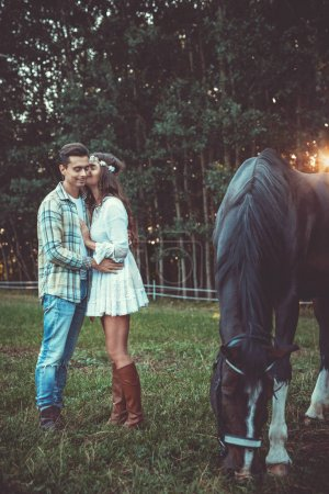 Young and happy couple in embrace on the meadow with a horses