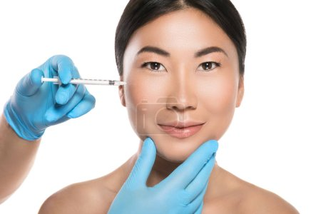 Asian woman is receiving facial injections. Isolated on white background
