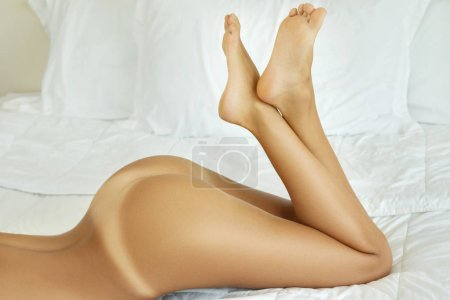 Female feet and buttocks in the bed