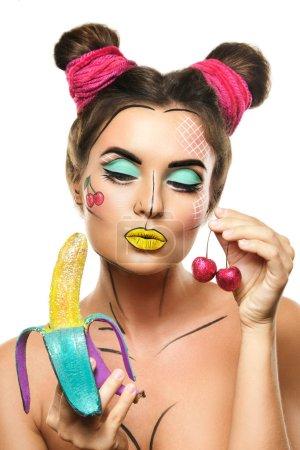 Beautiful model with creative pop art makeup holding banana and cherry