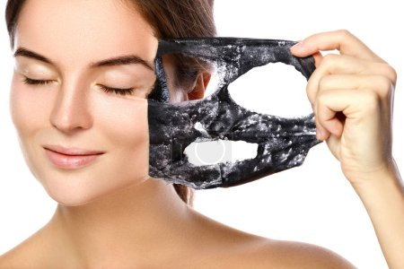 Hermosa mujer está quitando la máscara purificadora de su cara sobre fondo blanco
