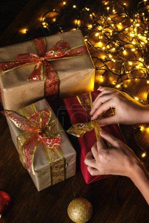 Photo pour Mains et cadeaux de Noël avec beaucoup de lumières rougeoyantes - image libre de droit