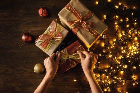 Foto de Las manos y los regalos de Navidad con muchas luces brillantes - Imagen libre de derechos