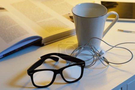 Photo pour Différents objets sur le bureau - Coupe de boissons chaudes, lunettes, livres et écouteurs - image libre de droit