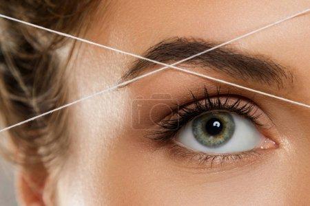 """Photo pour Gros plan de l """"œil féminin avec un fil. Filetage des sourcils - procédure d'épilation pour la correction de la forme des sourcils - image libre de droit"""