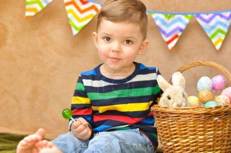Photo pour Un mignon petit garçon dans un raglan rayé brillant s'assoit près avec un panier où sont les oeufs de Pâques et un petit lapin en peluche. Un garçon mange une sucette verte. - image libre de droit