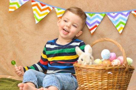 Photo pour Un mignon petit garçon dans un raglan rayé brillant s'assoit près avec un panier où sont les oeufs de Pâques et un petit lapin en peluche. Un garçon souriant et mange une sucette verte. - image libre de droit