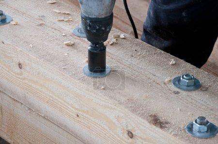 Photo pour Le processus de fermeture des boulons sur une poutre en bois. Fixation des poutres en bois entre eux. - image libre de droit