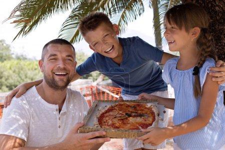 Photo pour Papa mignon avec des enfants tenant une pizza - image libre de droit