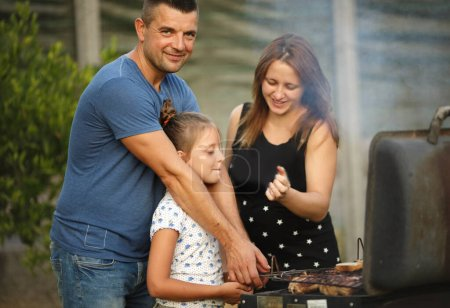 Photo for Family, food ang leisure concept. Family  cooking meat on barbecue grill in the garden  at summer - Royalty Free Image