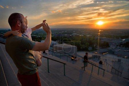 Photo pour Homme avec une petite fille dans les bras, regardant le coucher du soleil sur Montréal un soir d'été. Soins parentaux, père voyage avec sa fille. Voyage du Canada . - image libre de droit