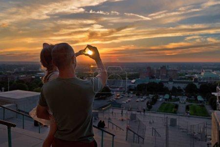 Photo pour Homme avec une petite fille dans les bras, admirant le coucher du soleil sur Montréal un soir d'été. Parent, père voyage avec sa fille. Voyage au Canada . - image libre de droit