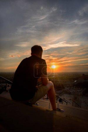 Photo pour Homme, un homme assis sur un escalier regardant le coucher du soleil au-dessus de Montréal un soir d'été. Voyage au Canada . - image libre de droit