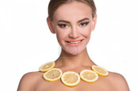 Photo pour Verticale de jeune femme posant avec des tranches oranges sur le fond blanc - image libre de droit