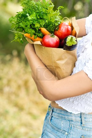 Photo for Woman holding paper bag with fresh organic vegetables - Royalty Free Image