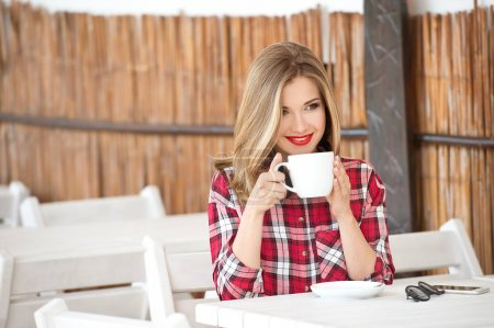 Photo for Young woman in red checkered shirt drinking coffee in cafe - Royalty Free Image