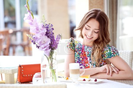 Photo for Beautiful smiling woman in summer dress sitting in cafe and drinking coffee - Royalty Free Image