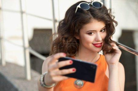 Photo pour Jeune femme faisant un autoportrait à l'aide d'un smartphone. Fille se faisant du mal - image libre de droit