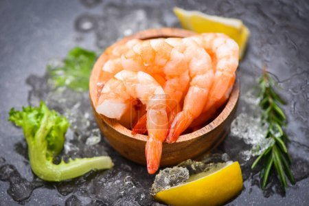 Photo pour Boiled shrimps prawns on ice frozen at the seafood restaurant fresh shrimp on dark plate with lemon rosemary ingredients herb and spices for cooking seafood - image libre de droit