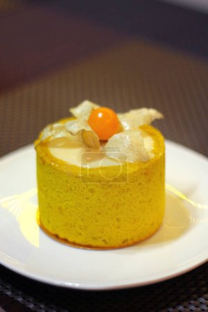 Photo for Mango cheesecake in a cafe on a white plate decorated with physalis. - Royalty Free Image