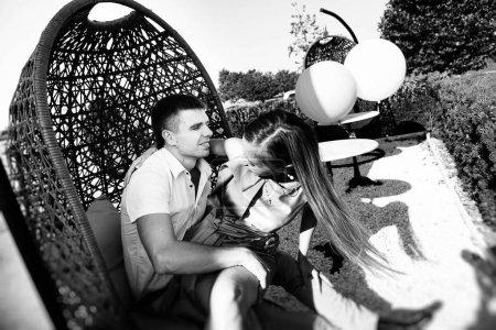 Foto de Feliz pareja de enamorados abrazándose en una silla-hamaca, tiernas y positivas las emociones - Imagen libre de derechos