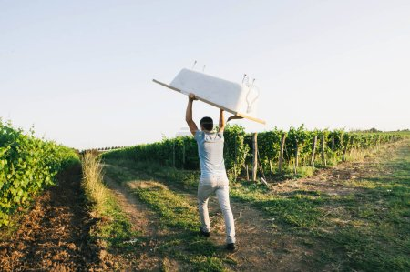 Photo for Man carries a bath over his head in the vineyards - Royalty Free Image