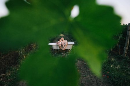 Photo for A man and a woman are sitting in a bath with rose leaves in the middle of the vineyards - Royalty Free Image