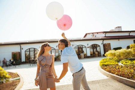 Photo pour Les amateurs sont rire et étreignant une promenade en été, tenant des ballons - image libre de droit