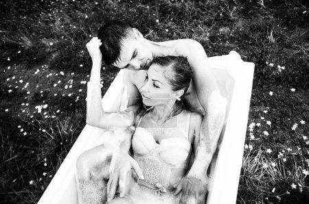 Foto de Un hombre y una mujer están sentados en un baño con hojas de color de rosa en medio de los viñedos - Imagen libre de derechos