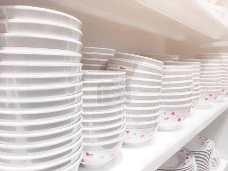 Photo pour Empilements de plaques blanches bien rangées sur les étagères dans le magasin - image libre de droit