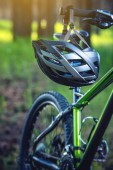 Sports helmet on a green mountain bike in the Park among the trees. Concept protection during active and healthy lifestyle
