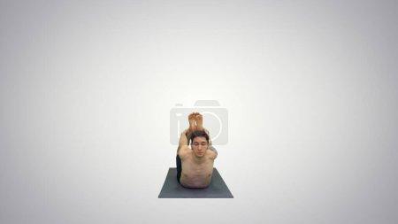 Hemdloser athletischer Mann demonstriert eine Yoga-Bogenpose auf Matte auf gr