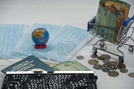 Photo pour Quarantaine au Kazakhstan. De l'argent avec des masques médicaux, un globe, une carte et un passeport sont sur la table. La fermeture des frontières et les voyages au Kazakhstan. - image libre de droit