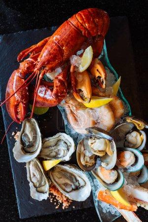 Foto de Vista superior de ostras, camarones congelados, moluscos y langosta roja grande con rodajas de limón sobre fondo de piedra - Imagen libre de derechos