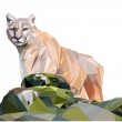 Light brown cougar stands behind the stones, low p...