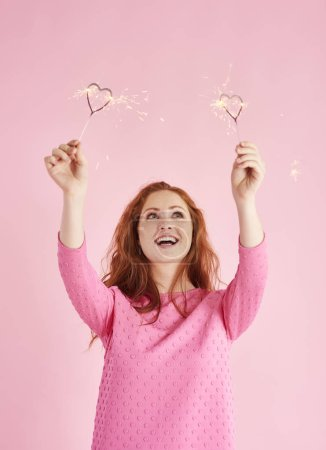 Photo for Woman holding heart shaped sparkler and looking up at studio - Royalty Free Image