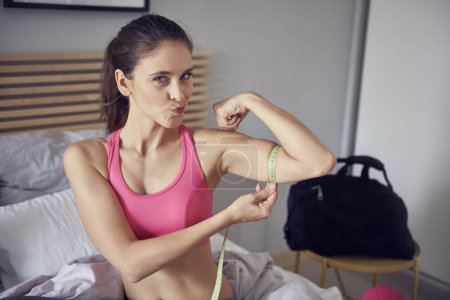 Photo for Portrait of slim woman measuring her biceps - Royalty Free Image