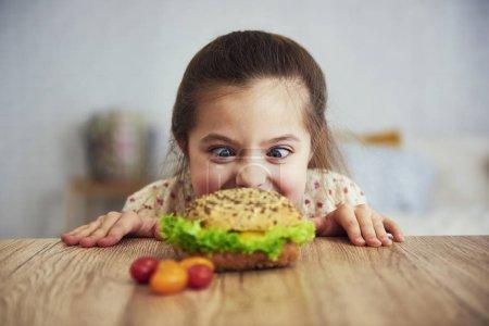 Photo for Playful girl looking at delicious hamburger - Royalty Free Image