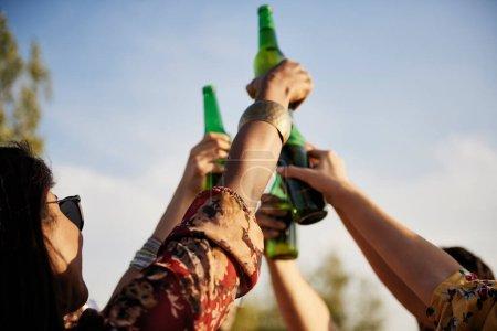 Photo pour Groupe de personnes qui portent un toast de fête avec des bouteilles de bière - image libre de droit