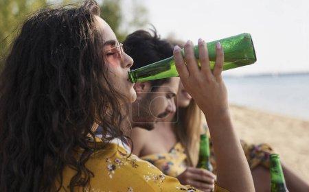 Photo pour Gros plan de fille buvant de la bière avec des amis sur la plage . - image libre de droit