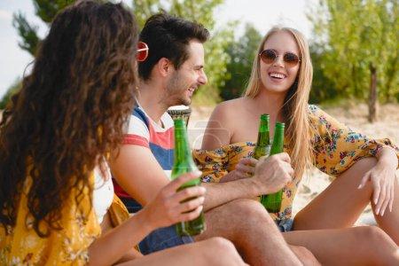 Photo pour Groupe d'amis passant du bon temps avec des bouteilles de bière - image libre de droit