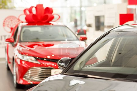 Photo for New cars for sale at the dealership salon, copy space. Beautiful shiny red modern sedan with a big bow on the roof. Present gift car at the showroom. Buying new car concept. Winning car advertisement - Royalty Free Image