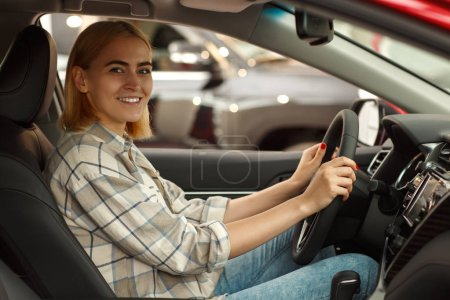 Photo for Happy beautiful young woman sitting in a car at the dealership smiling to the camera holding steering wheel, copy space. Gorgeous female driver sitting comfortably in a modern automobile for sale - Royalty Free Image