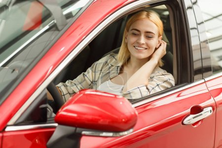 Photo for Gorgeous happy woman fixing her hair looking in the side mirror, sitting in her car. Attractive woman driving her new automobile. Cheerful female driver travelling by car. Vacation, travel concept - Royalty Free Image