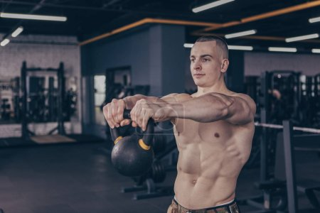 Photo for Attractive ripped male athlete with muscular sexy body exercising with kettlebell at the gym. Shirtless crossfit sportsman working out with weights at sports studio, copy space. Crossfit concept - Royalty Free Image