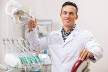 Photo for Happy handsome male dentist smiling joyfully, working at his office, copy space. Professional dentist waiting for patients at his clinic. Dental examination, dentistry and medical industry concept - Royalty Free Image